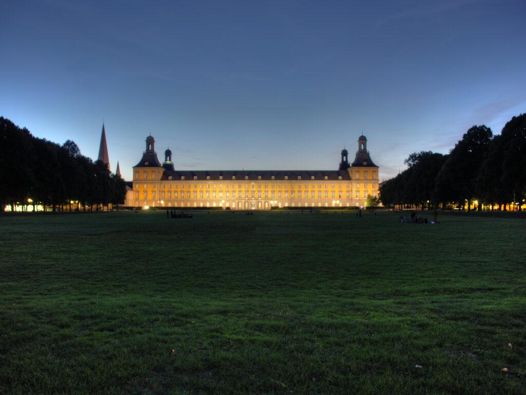 Das gelbe Universäsitasgebäude am Abend angestrahlt vor dunkelblauem Himmel